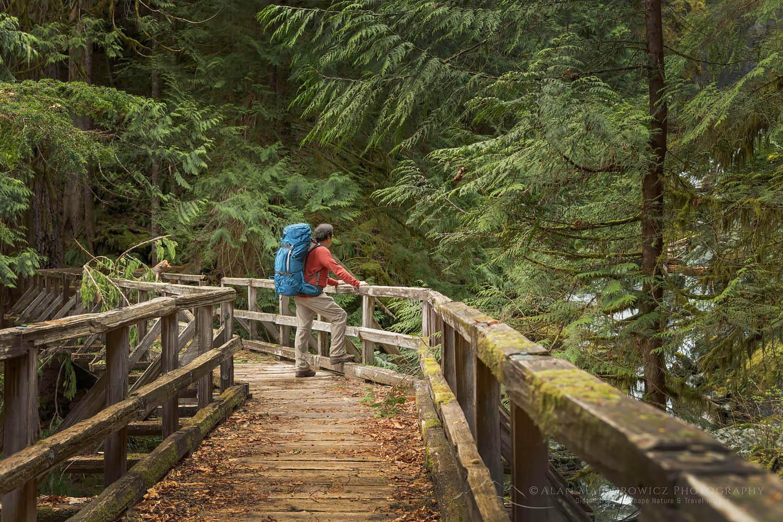 Backpacker on bridge over Hidden Creek Baker lake Trail North Cascades