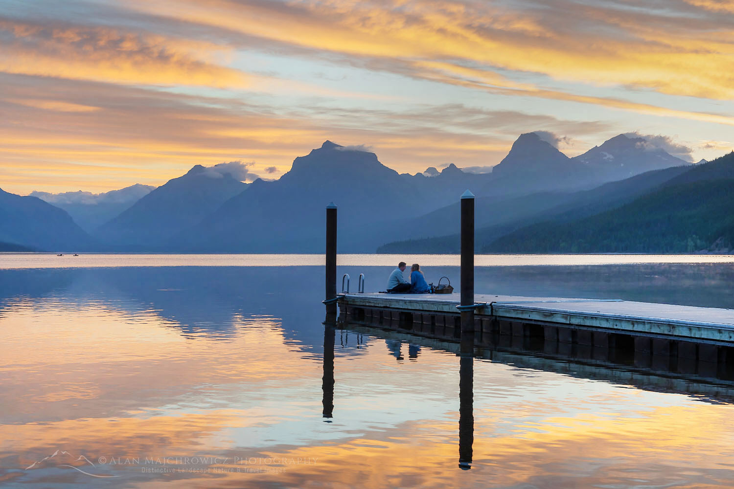 Couple on dock at Sunrise at Lake McDonald Glacier National Park Montana