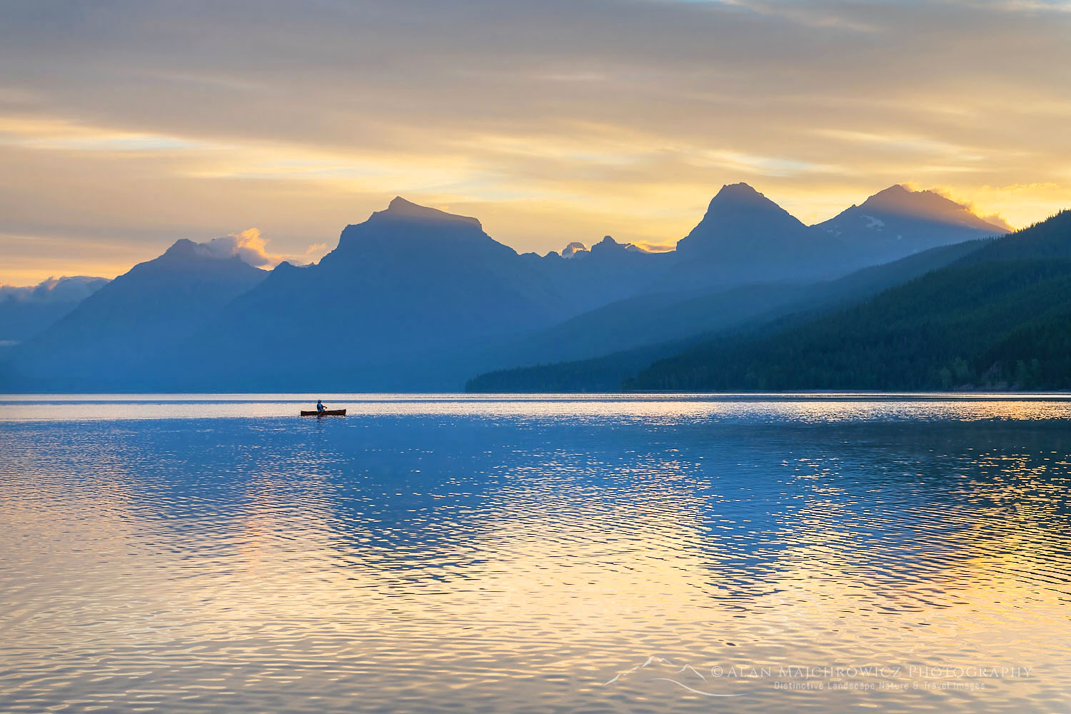 Canoeist paddling on Lake McDonald at sunrise. Glacier National Park Montana